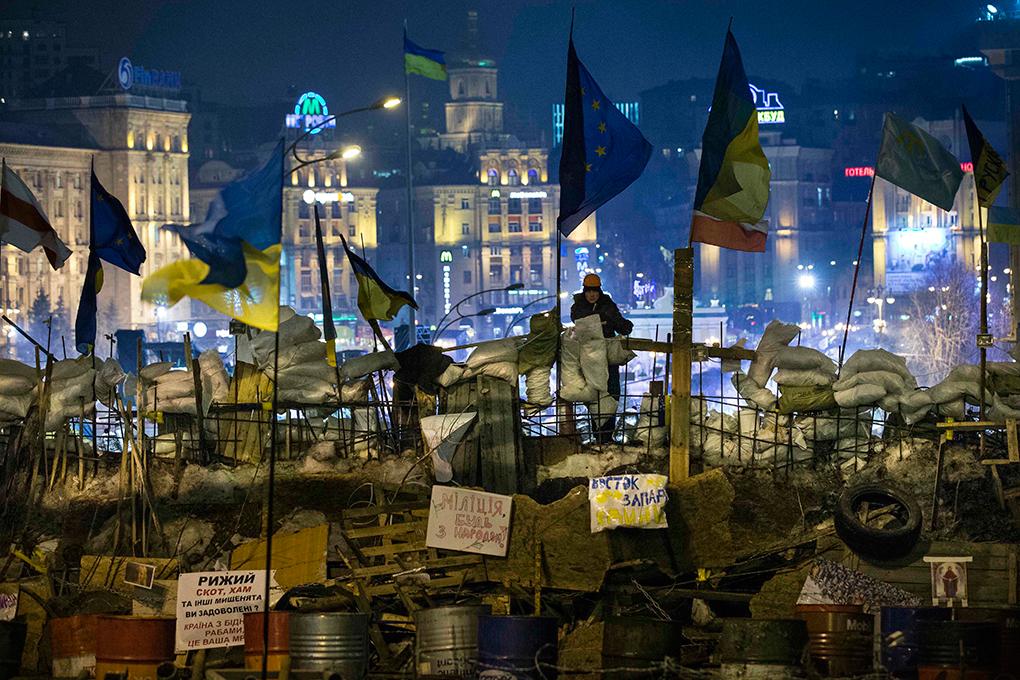 Un activista de la Unión Pro-Europea vigila la cima de las barricadas que rodean un campamento fortificado durante un mitin en la Plaza de la Independencia en Kiev, Ucrania, Martes, 17 de diciembre 2013. AP PHOTO/ALEXANDER ZEMLIANICHENKO